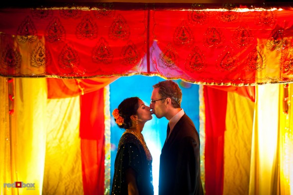 Karthik and Mike kiss beneath the canopy where their Hindu and Jewish wedding ceremonies took place at the Uptown Hideaway in Seattle. (Photo by Dan DeLong/Red Box Pictures)