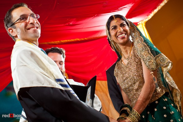 Mike and Karthik smile at their guests during their Jewish wedding ceremony at the Uptown Hideaway in Seattle. (Photography by Dan DeLong/Red Box Pictures)