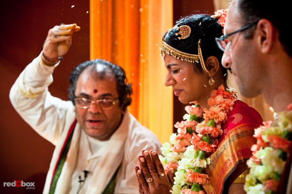 Pundit Mahesh Shastri tosses rice toward Karthik and Mike during their Indian wedding ceremony at the Uptown Hideaway in Seattle. (Photography by Andy Rogers/Red Box Pictures)