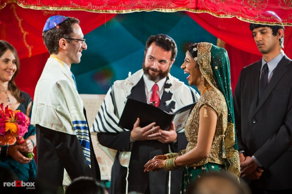 Mike and Karthik laugh as Rabbi Olivier Benhaim performs their Jewish wedding ceremony at the Uptown Hideaway in Seattle. (Photography by Andy Rogers/Red Box Pictures)
