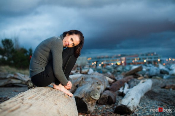 Liz sits atop drift logs while posing for portraits on a Seattle beach a a spring evening. (Photo by Dan DeLong/Red Box Pictures)