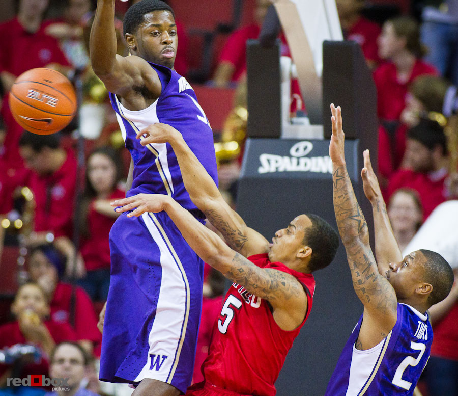 The University of Washington Huskies forward Matthew Bryan-Amaning and guard Isaiah Thomas defend against Seattle University Redhawks guard Cervante Burrell at Key Arena in Seattle Tuesday, Feb. 22, 2011. (Photo by Andy Rogers/Red Box Pictures)