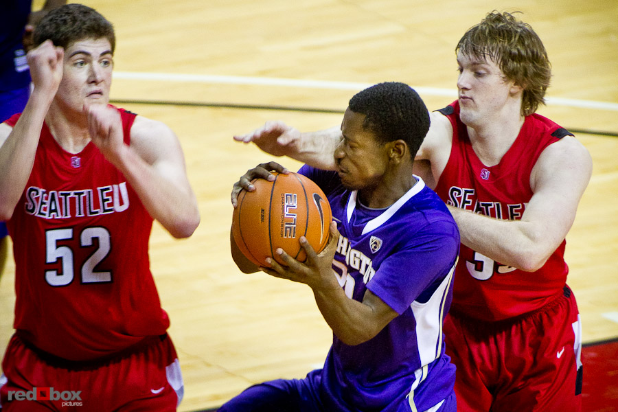 The University of Washington Huskies Terrence Ross take a shot in the face from Seattle University Redhawks defender Gavin Gilmore as Alex Jones looks on at Key Arena in Seattle Tuesday, Feb. 22, 2011. (Photo by Andy Rogers/Red Box Pictures)