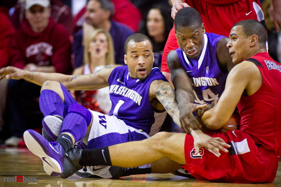 The University of Washington Huskies Venoy Overton and Darnell Gant battle Seattle University Redhawks forward Aaron Broussard for the ball at Key Arena in Seattle Tuesday, Feb. 22, 2011. (Photo by Andy Rogers/Red Box Pictures)